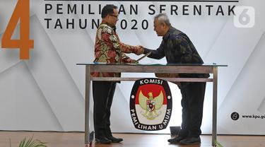 Mendagri, Tito Karnavian (kiri) dan Ketua KPU Arief Budiman saat Serah Terima Data Penduduk Potensial Pemilih Pemilihan (DP4) untuk Pemilihan Serentak 2020 di Jakarta, Kamis (23/1/2020). Kemendagri menyerahkan DP4 dengan jumlah 105 juta. (Liputan6.com/Herman Zakharia)