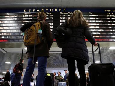 Wisatawan melihat papan jadwal perjalanan di Pennsylvania Station, New York City, Rabu (23/11). Di Amerika Serikat, tradisi mudik dilakukan saat hari perayaan Thanksgiving yang jatuh setiap Kamis keempat di November. (REUTERS/Brendan McDermid)