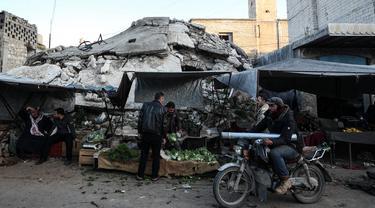 Warga Suriah membeli produk makanan di pasar menjelang buka puasa pada hari kedua bulan suci Ramadhan, di kota Ariha yang dilanda perang, di provinsi Idlib, Kamis (15/4/2021). Mereka menjalankan Ramadhan di antara lautan reruntuhan bekas konflik gencatan senjata. (Omar HAJ KADOUR/AFP)