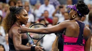 Petenis Serena Williams (kiri) menghampiri kakak perempuannya, Venus Williams usai bertanding di putaran ketiga turnamen tenis AS Terbuka di New York, Jumat (31/8). Serena mengalahkan Venus dengan skor 6-1, 6-2. (AP Photo/Adam Hunger)