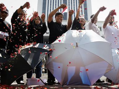 Sejumlah massa yang tergabung dalam Koalisi Masyarakat Sipil Penegak Citra DPD menaburkan bunga pada payung sebagai bentuk simbol kekhawatiran matinya keadilan dan penegakan hukum di depan Mahkamah Agung, Jakarta, Rabu (7/6). (Liputan6.com/Faizal Fanani)