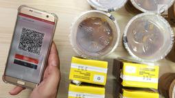Model menggunakan barcode untuk pembayaran pada aplikasi  berbasis mobile yang menawarkan inovasi konsep restoran digital pertama di Indonesia saat Soft Launching Aplikasi MeeberLite dan Meeberian di Jakarta, Selasa (31/7). (Liputan6.com)
