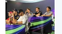 Rio Haryanto terlihat duduk santai diatas Lewis Hamilton dan Sebastian Vettel saat mengikuti sesi press conference jelang balapan Formula 1 2016 di Sirkuit Alber Park, Australia, Kamis (17/3/2016). (bola.com/Twitter/Manor Racing)