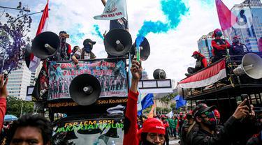 Massa buruh menyalakan asap suar saat unjuk rasa di Patung Kuda, Jakarta, Kamis (22/10/2020). Aksi gabungan buruh, petani, mahasiswa, dan pelajar dilakukan untuk menyuarakan penolakan pengesahan UU Cipta Kerja dan meminta Presiden mengeluarkan Perppu. (Liputan6.com/Faizal Fanani)