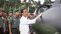 Presiden Jokowi meraba bodi sebuah helikopter di Pameran  Alutsista TNI AD, Jakarta, Rabu (17/12/2014). (LIputan6.com/Faizal Fanani)