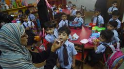 Pekerja kesehatan Pakistan memberi vaksin polio ke seorang anak di Karachi (9/4). Pakistan adalah salah satu dari hanya dua negara di dunia di mana polio, penyakit masa kecil yang melumpuhkan. (AFP Photo/Rizwan Tabassum)