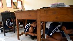 Sejumlah siswa berlindung di bawah meja saat mengikuti simulasi gempa bumi dan tsunami di Jimbaran, Bali (5/11/2019). Seperti diketahui, gempa bumi bawah laut berkekuatan 9,1 SR pada tahun 2004 lalu telah memicu tsunami yang menewaskan lebih dari 170.000 orang. (AFP Photo/Sonny Tumbelaka)