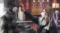 Verdi Olha dari Ukraina mengukur suhu tubuh pelajar lain di Universitas Chongqing di Chongqing, China, 18 Februari 2020. Sejumlah pelajar asing di Chongqing ambil bagian dalam kampanye pengendalian epidemi dengan terlibat dalam pekerjaan sukarela. (Xinhua/Wang Quanchao)
