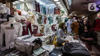 Pedagang melayani pembeli di Pasar Tanah Abang, Jakarta, Selasa (6/4/2021). Menjelang bulan Ramadan, Pasar Tanah Abang mulai dipadati pengunjung untuk berbelanja busana, namun menurut pedagang jumlah pengunjung bulan Ramadan kali ini tidak seramai sebelum pandemi Covid-19. (Liputan6.com/Johan Tallo)