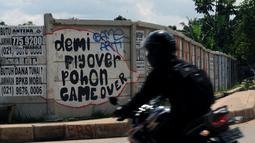 Salah satu pesan bernada satire dilukiskan di tembok pembatas yang ada di Jalan Juanda, Depok, Jawa Barat. Foto diambil pada Senin (2/3/2015). (Liputan6.com/Helmi Fithriansyah)