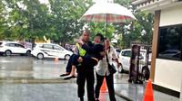 Seorang polisi menggendong nenek yang kehujanan ketika menyeberang ke gereja Maranatha, Cilacap. (Foto: Liputan6.com/Polres Cilacap/Muhamad Ridlo)
