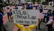 Massa yang tergabung dalam Front Perjuangan Rakyat (FPR) membawa poster saat berunjuk rasa di Jalan Gerbang Pemuda, Senayan, Jakarta, Jumat (14/8/2020). Dalam aksinya mereka menolak rencana pengesahan RUU Cipta Kerja atau omnibus law. (Liputan6.com/Faizal Fanani)