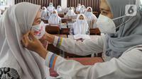 Petugas Sudinkes Jakarta Selatan melakukan kegiatan sosialisasi 3M (memakai masker, mencuci tangan dengan sabun, dan menjaga jarak) kepada para santri di Ponpes Daarul Rahman, Jagakarsa, Rabu (18/11/2020). Sosialisasi 3M tersebut disertai pembagian 3500 masker kain 3 lapis. (merdeka.com/Arie Basuki)