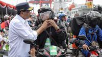 Menhub Budi Karya Sumadi memasangkan helm peserta mudik gratis sepeda motor saat menyambut kedatangan mereka di Pelabuhan Tanjung Priok, Rabu (20/6). Ada 699 sepeda motor dan 1.650 penumpang kembali ke Jakarta dari Semarang. (Liputan6.com/Faizal Fanani)