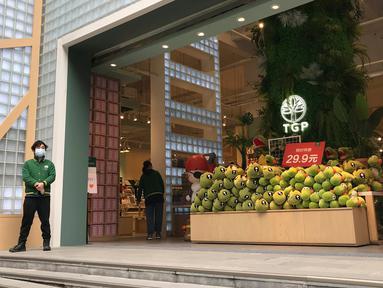 Penjaga toko menunggu pelanggan di sebuah jalan ritel di Wuhan di provinsi Hubei, China tengah (30/3/2020). Para pemilik toko di kota yang menjadi pusat wabah virus corona (Covid-19) itu mulai buka kembali usahanya pada Senin, tapi para pelanggannya masih tampak sepi. (AP Photo/Olivia Zhang)