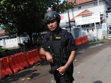 Polisi bersenjata laras panjang berjaga di dekat pintu masuk dermaga Wijayapura menuju LP Nusakambangan, Cilacap, Jateng, Kamis (28/7). 1.466 personel gabungan disiagakan untuk melakukan pengamanan eksekusi mati tahap III. (Liputan6.com/Helmi Afandi)
