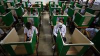 Para siswa dengan mengenakan masker duduk di mejanya yang menggunakan partisi di Samkhok School di Pathum Thani, Bangkok, Rabu (1/7/2020). Thailand memulai fase kelima relaksasi pembatasan covid-19 yang memungkinkan pembukaan kembali sekolah-sekolah setelah ditutup sejak Maret. (AP/Sakchai Lalit)