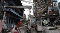 Polisi mengamankan sekitar gedung yang ambruk di Jalan Brigjen Katamso, Kota Bambu Selatan, Palmerah, Jakarta Barat, Senin (6/1/2020). Tiga orang dilaporkan terluka akibat tertima material gedung empat lantai tersebut. (Liputan6.com/Johan Tallo)