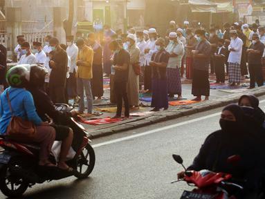 Sepeda motor melintas saat umat muslim melaksanakan salat Idul Adha 1442 H di Masjid Masjid Jami Al-Mubarok, Tangerang, Banten, Selasa (20/7/2021). Sebagian masjid melakukan pelaksanaan salat Idul Adha 1442 H, namun dengan protokol kesehatan yang ketat. (Liputan6.com/Angga Yuniar)