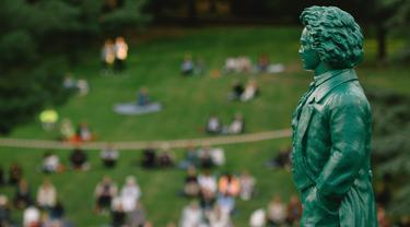 Warga menikmati konser yang diselenggarakan oleh Beethoven Orchestra Bonn di sebuah taman di Bonn, Jerman, pada 28 Juni 2020. Konser tu digelar untuk memperingati 250 tahun kelahiran komponis sekaligus pianis Ludwig van Beethoven. (Xinhua/Tang Ying)