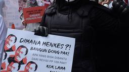Massa Aliansi Koalisi Masyarakat Peduli Kesehatan (KOMPAK) mengenakan kostum Anonymous saat menggelar aksi di depan Kementerian Kesehatan, Jakarta, Kamis (26/11/2020). (Liputan6.com/Herman Zakharia)
