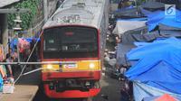 Kereta commuter line melintas di rel KRL Nambo yang dipadati aktivitas jual beli pasar dadakan, Citeureup, Bogor (20/4). Pasar dadakan ini digelar setiap hari Jumat. (Merdeka.com/Arie Basuki)