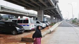 Seorang wanita melintas dekat sejumlah mobil yang terparkir di bawah kolong tol Becakayu Kalimalang, Jakarta Timur, Selasa (12/2). Lahan kosong di bawah kolong tol Becakayu disalahgunakan menjadi parkir liar. (Liputan6.com/Faizal Fanani)