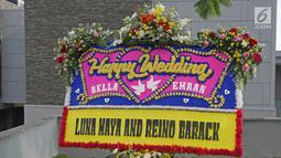 Karangan bunga dari aktris Luna Maya terpajang di lokasi resepsi kedua pernikahan Laudya Cynthia Bella dan Engku Emran di kawasan Dago, Bandung, Minggu (8/10). Bella dan Emran resmi menikah pada 8 September 2017 di Malaysia. (Liputan6.com/Herman Zakharia)