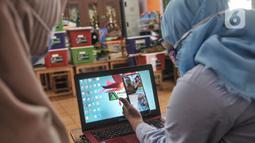 Pendidik membimbing murid saat kelas sentra seni secara virtual di PAUD Cempaka, Jakarta, Senin (23/11/2020). Selama Covid-19, kegiatan belajar virtual melalui kelas sentra atau praktik digelar guna meningkatkan kreativitas dan daya tangkap meski belajar dari rumah. (merdeka.com/Iqbal S Nugroho)