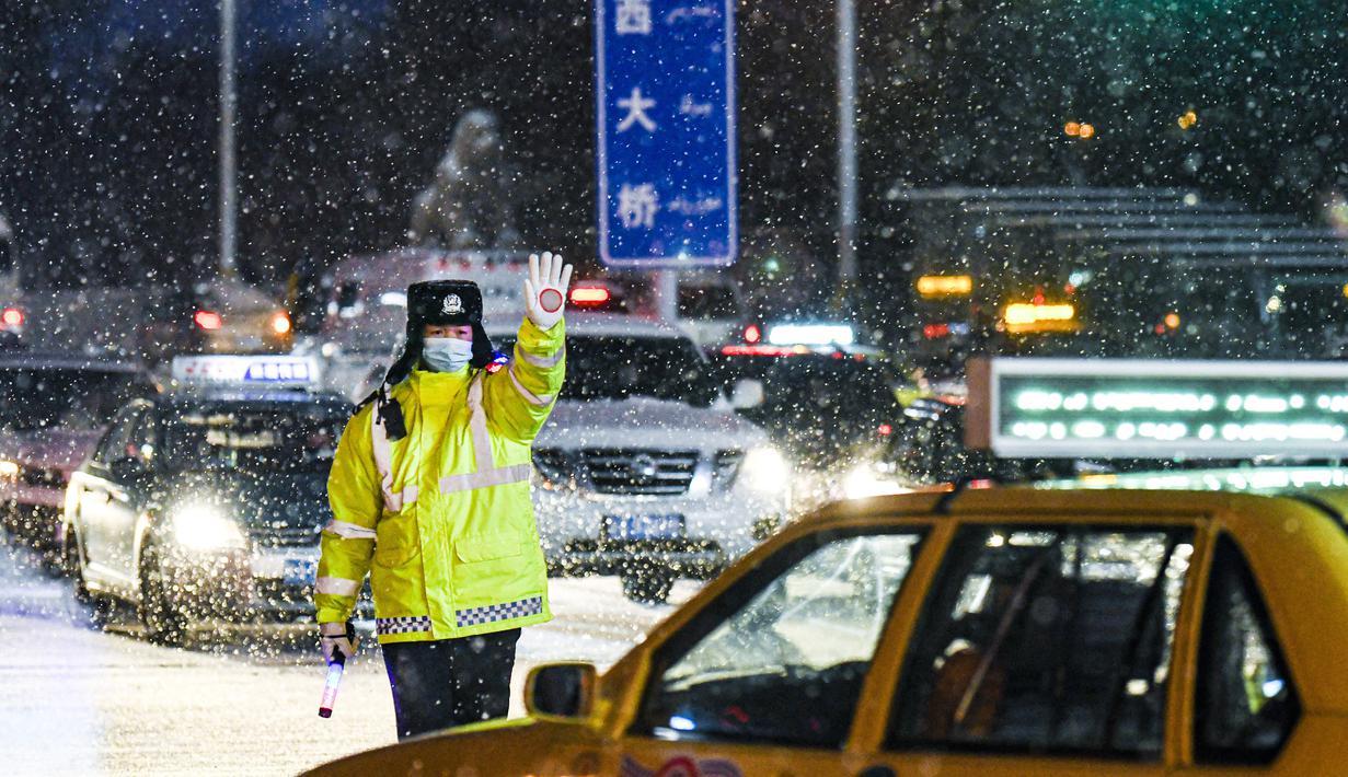 Polisi bertugas di tengah hujan salju di Urumqi, ibu kota Daerah Otonom Uighur Xinjiang, China barat laut, pada 19 November 2020. Hujan salju yang terus turun selama berhari-hari telah menyebabkan jalanan di Kota Urumqi basah dan licin. (Xinhua/Wang Fei)