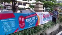 Seoerang pria memasang spanduk untuk acara perpajangan SIM A dan C secara gratis yang bertepat dengan acara Kartini Run 2018. (istimewa)