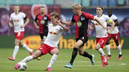 Pemain RB Leipzig, Daniel Carvajal, berebut bola dengan pemain Hertha Berlin, Per Skjelbred, pada laga  Bundesliga di Red Bull Arena, Rabu (27/5/2020). Kedua tim bermain imbang 2-2. (AP/Alexander Hassenstein)