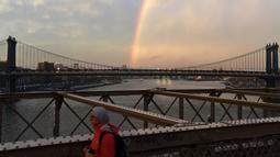Warga beraktivitas saat pelangi terlihat dari Jembatan Brooklyn di New York City, AS (15/5). Jembatan ini adalah jembatan suspensi terpanjang di dunia sejak pembukaannya hingga 1903, serta jembatan suspensi kabel baja pertama. (AFP Photo/Hector Retamal)
