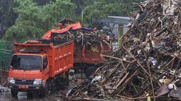Petugas menutupi sampah yang telah dimasukkan ke dalam bak truk pengangkut di Pintu Air Manggarai, Jakarta, Rabu (24/4). Tingginya curah hujan di Bogor membuat sampah yang berasal kebanyakan dari sampah rumah tangga ini terbawa arus sungai menumpuk di Pintu Air Manggarai. (Liputan6.com/Johan Tallo)