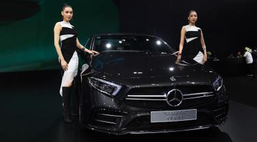 "Dua model berpose di samping Mercedes Benz CLS 53 2019 selama Thailand International Motor Expo di Bangkok (29/11). Thailand International Motor Expo bertema ""Enjoy Driving! Before Driverless Era"".  (AFP Photo/Lillian Suwanrumpha)"