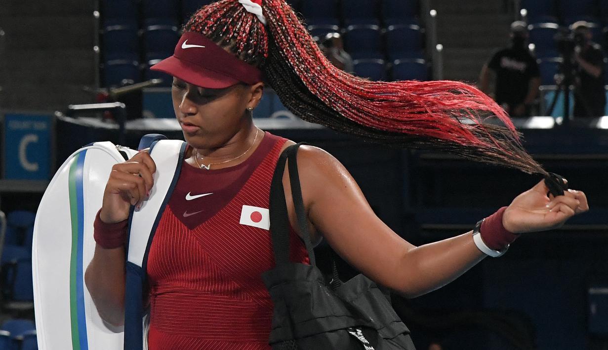Petenis Jepang Naomi Osaka meninggalkan lapangan setelah dikalahkan Marketa Vondrousova dari Republik Ceko dalam pertandingan tenis putaran ketiga tunggal putri Olimpiade Tokyo 2020 di Ariake Tennis Park di Tokyo (27/7/2021). Naomi kalah dari Marketa Vondrousova 6-1, 6-4. (AFP/Tiziana Fabi)