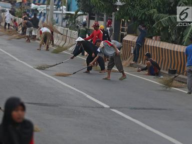 Warga berebut uang yang dilemparkan pengguna jalan menggunakan sapu di Jembatan Sewo, Indramayu, Jawa Barat, Senin (3/6/2019). Kehadiran pencari sedekah tersebut biasanya kian bertambah banyak saat menjelang arus mudik Lebaran. (Liputan6.com/Herman Zakharia)