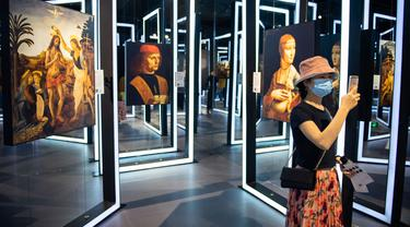 Seorang pengunjung mengabadikan gambar dalam sebuah pameran seni bertajuk Tribute to da Vinci yang digelar di gedung Changsha IFS, Changsha, Provinsi Hunan, China, Senin (4/5/2020). (Xinhua/Chen Sihan)