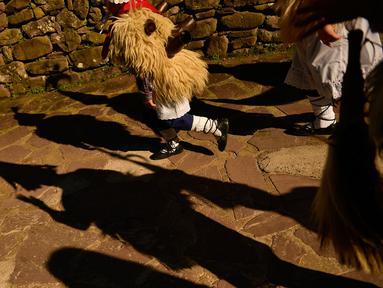 Seorang anak mengenakan kostum dengan latar belakang bayangan peserta karnaval di antara desa Pyrenees Ituren dan Zubieta, Spanyol (29/1). Acara ini merupakan salah satu karnaval paling kuno di Eropa. (AP Photo / Alvaro Barrientos)