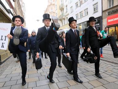 Sejumlah pria mengenakan kostum berjalan dengan mengangkat tinggi kakinya di Brno, Republik Ceko (7/1). Mereka berjalan dengan mengenakan kostum tersebut dalam acara International Silly Walk Day.  (AFP Photo/Radek Mica)