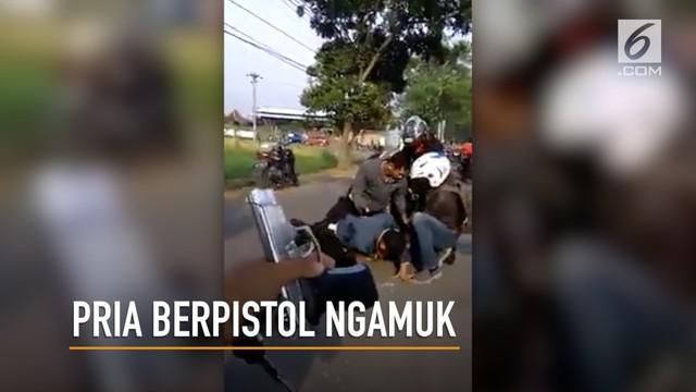 Seorang pria berpistol mengancam keselamatan warga di tengah jalan.