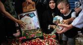 Cucu aktris senior Titi Qadarsih menuangkan air ke pusara sang nenek saat pemakaman di TPU Tanah Kusir, Jakarta, Selasa (23/10). Titi menghembuskan nafas terakhir pada Senin, 22 Oktober 2018. (Liputan6.com/Faizal Fanani)