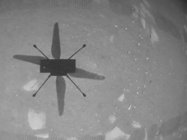 Helikopter Ingenuity melayang di atas permukaan planet Mars saat penerbangan pertama bertenaga dan terkontrol di planet lain pada 19 April 2021. h(Handout/NASA/JPL-CALTECH/AFP)