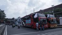 Penyedia bus dan stakeholder pariwisata di Kabupaten Pati menggelar konvoi sambil mengibarkan bendera putih, tanda menyerah dengan kebijakan PPKM. (Liputan6.com/ Ahmad Adirin)