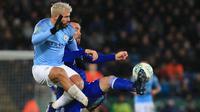 Striker Manchester City, Sergio Aguero, berebut bola dengan bek Leicester, Christian Fuchs, pada laga Piala Liga di Stadion King Power, Leicester, Selasa (18/12). Leicester kalah adu penalti dari City. (AFP/Lindsey Parnaby)