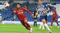 Gelandang Liverpool, Mohamed Salah, berebut bola dengan bek Brighton, Dan Burn, pada laga lanjutan Premier League pekan ke-34 di Stadion Falmer, Kamis (9/7/2020) dini hari WIB. Liverpool menang 3-1 atas Brighton. (AFP/Daniel Leal-Olivas/pool)