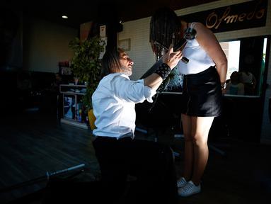 Penata rambut, Alberto Olmedo memotong rambut pelanggannya menggunakan katana di Madrid, Spanyol, 29 Desember 2018. Pria tersebut memilih menggunakan pedang samurai, api dan cakar besi untuk mewujudkan gaya rambut impian pelanggan. (AP/Manu Fernandez)