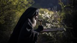 Seorang imam Ortodoks Bulgaria memimpin prosesi keagamaan tahunan di Biara Bachkovo, Bulgaria (9/4). Prosesi ini digelar setiap tahun pada hari kedua Paskah Ortodoks. (AFP Photo/Nikolay Doychinov)