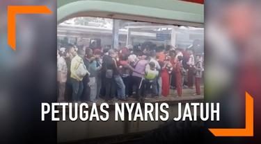 Desakan antrean di peron stasiun membuat seorang petugas nyaris jatuh ke rel kereta.