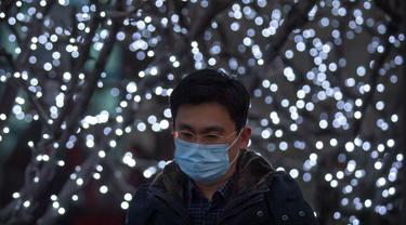 eorang pria mengenakan masker berjalan melewati pameran lampu di kawasan pusat bisnis di Beijing, Selasa (12/1/2021).  Para ahli dari WHO akan tiba di China minggu ini untuk penyelidikan yang telah lama diantisipasi mengenai asal-usul pandemi virus corona. (AP Photo/Mark Schiefelbein)
